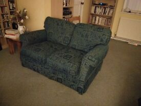 Lovely dark green two seater sofa with lighter green etched style pattern