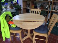 Round rubberwood table with dropsides; 4 matching wooden chairs with tie-on cushions
