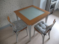 GLASS TOPPED WOODEN TABLE WITH 2 CHAIRS + SEAT CUSHIONS