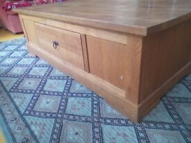 A brilliant coffee table/chest made of solid oak in good condition. It contains one draw.