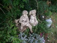 Boy and girl stone statues on bench
