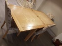 Solid wood 6 seater dining table and 4 fabric chairs. Immaculate condition