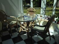 Glass table and three wicker chairs and cushions, ideal for conservatory or covered patio
