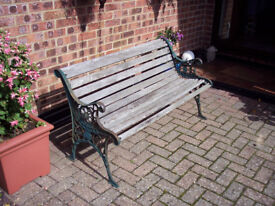 Garden bench with wooden slats and iron ends.