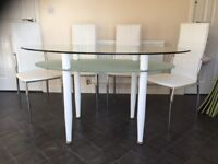 Clear glass oval kitchen dining table with under shelf and 4 chairs in white