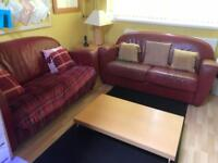 Two red leather look sofas and low coffee table