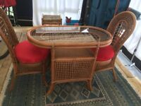Cane table with glass top and two cane chairs with padded seats