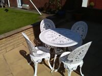 White cast iron antique replica table and 4 chairs.