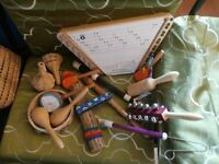 basket of musical instruments including rainstick, hand woven shakers and two flat guitars