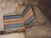 Rainbow coloured folding chair with wooden arm rests