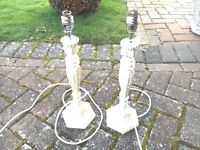 A pair of white ornate bedside lamps