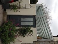 Aluminium lean-to greenhouse attached to two walls; horticultural glazing. Measures 14ft x 9 ft.