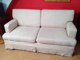 Cream fitted covers on red upholstered 3 seater sofa with tapering beechwood legs