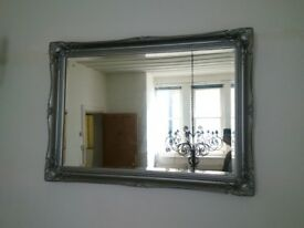 very large beveled edge mirror with substantial ornate silver frame can deliver