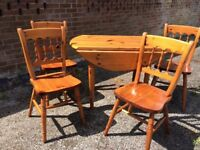 Pine, round, drop leaf dining room table with 4 pine chairs.
