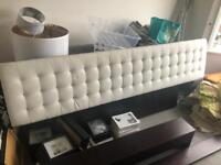 King size bed. White leather look padded headboard.