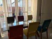 Stunning Harvey's 6 seater dining table. Glass table with wooden legs and multicoloured chairs.