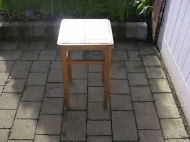 A four legged wooden stool with new vinyl cover on seat.