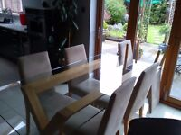 6 ft glass dining table with oak legs and 6 suede dining chairs