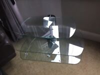 Clear glass Tv shelving unit with silver tower to conceal wires