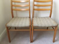 2 wooden chairs with oatmeal fabric seats.