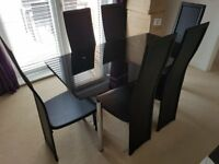 Black glass dining table and 6 chairs with matching side table