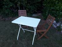White folding table and two folding chairs