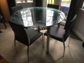 Glass and chrome round extending dining table with 4 chairs