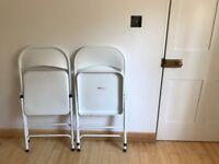 Set of four white folding chairs