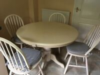 Table and chairs. Cream 108cm circular table 4chairs with cushions.