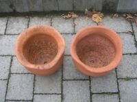 Two round terracotta planters with wavy tops.