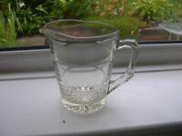 A heavy duty one lite capacity clear glass jug.