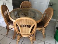 Circular glass-topped cane dining table with four matching cane chairs