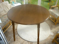 Round wooden dining table, seats 4 with folding sides.