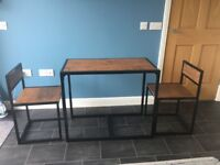 industrial look , space saving kitchen set , chairs slide into table .