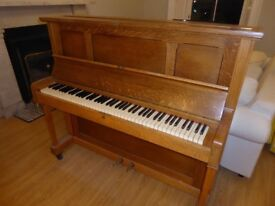 Traditional upright piano with full keyboard and brass foot pedals