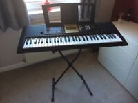 Electric Yamaha keyboard with folding stand and attachable sheet stand.