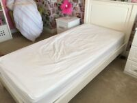White wooden single bed and mattress