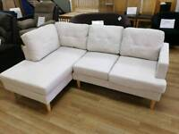Cream corner sofa with cushions and wooden legs