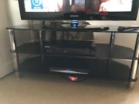 Black glass TV stand for sale. Good condition.