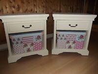 Pair of wooden bedside cabinets painted in clotted cream chalk paint each with floral storage box.