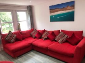 Corner Sofa for sale in red cloth fabric in good condition with cushions