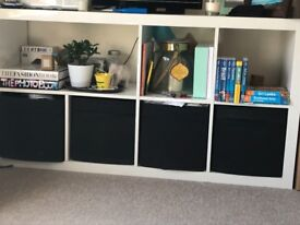 White storage unit complete with 4 black fabric storage boxes