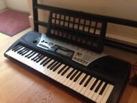 Yamaha keyboard with stand and books
