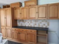 Various kitchen base and wall units including oak doors