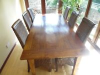 """Lg solid wood dining table, 2.2m x 1m (7'3' x 3'3""""), plus 6 high back rattan chairs & 1 easy chair."""