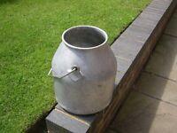 A used aluminium churn.
