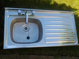 Stainless steel kitchen sink with taps for sale.
