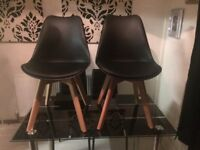 Dining or kitchen chairs in black with padded seats and contrasting wooden legs