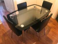 Glass and chrome dining table and four black chairs.